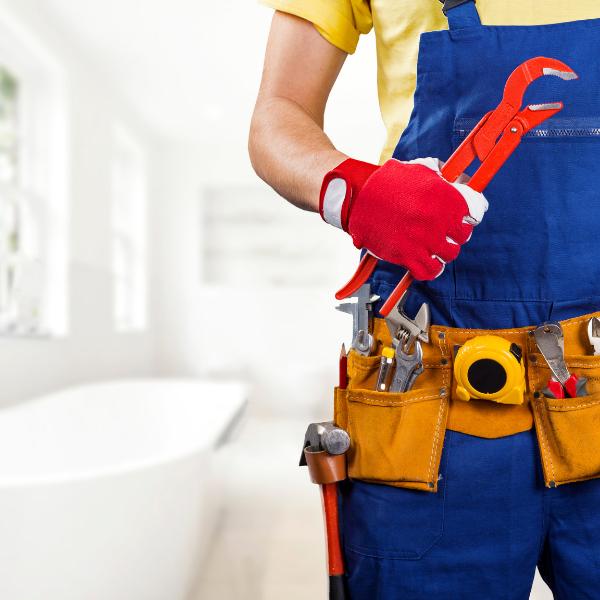 Plumber holding tools in bathroom